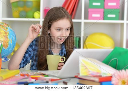 Cute  student girl at class with laptop and tea