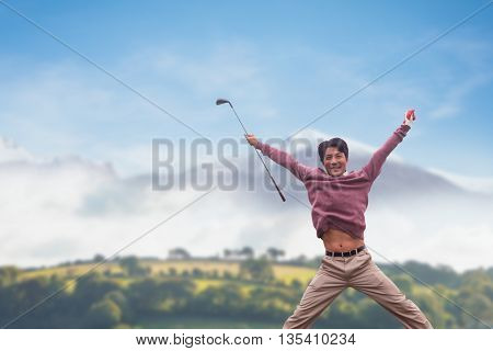 Man jumping with golf club against country scene