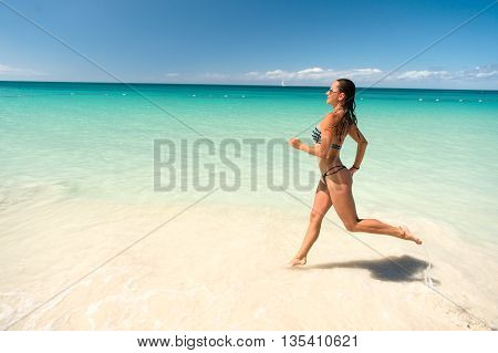 Young pretty woman with beautiful body in swimsuit running in ocean water sunny day outdoor