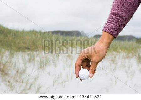 View of hand with golfball against view of sand