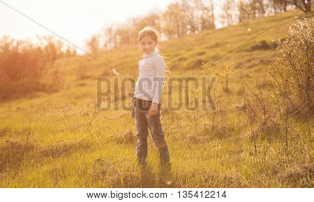 smiling little girl standing on sunlight in countryside on a hill