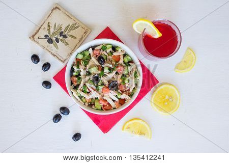 Greek salad with chicken with glass of cowberry fruit-drink