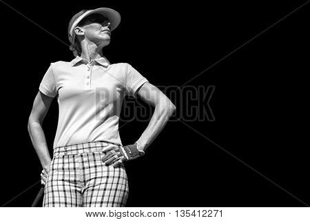 Woman playing golf against black background