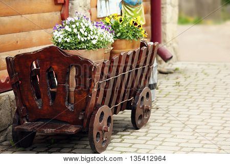 Yellow buckets with flowers in wooden cart