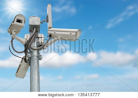 Group of security cameras (CCTV) or surveillance camera on pole isolated on blue sky background.