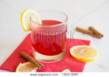 Cranberry juice with lemon and cinnamon on a red napkin