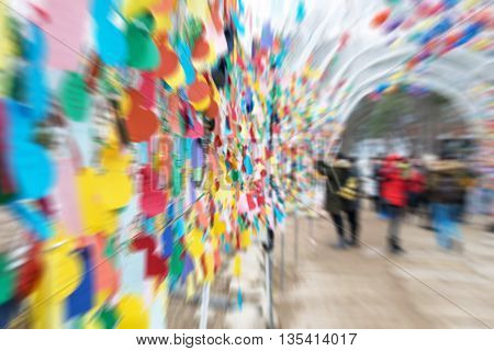 The blurred of people in the tunnel with hanging color paper notes.