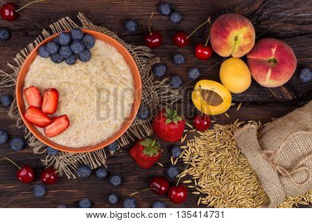 Breakfast with porridge strawberry cherry blueberry and apricots on a wooden table. Top view