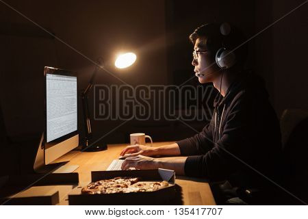 Focused asian man in headphones working with computer and eating pizza at the table in dark room