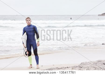 Portrait of young athletic male surfer wearing blue wetsuit, holding surfboard under his arm, standing on beach after morning surfing session - water sports concept. Baleal, Peniche, Portugal