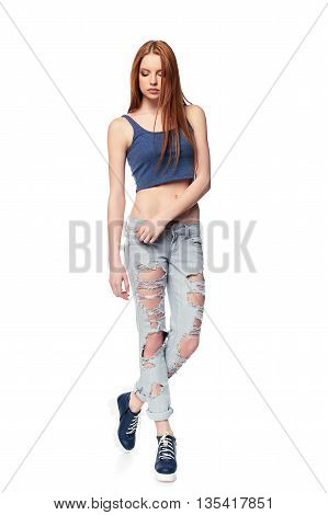 Modern red haired female wearing distressed jeans posing in full length over white background