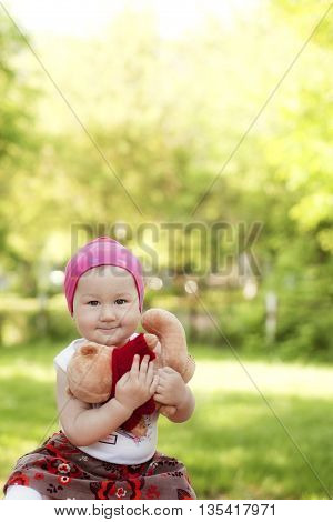 happy little girl in cap playing with Teddy bear in summer Park