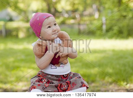 Little girl playing with a Teddy bear hugged him and not give greedy