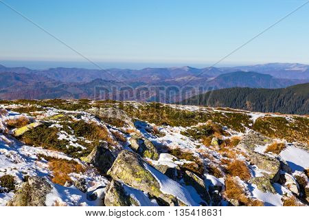 Snowbound Rocks and Yellow Grass and Foggy Mountain Hills on remote Background Sunny Day Clear Blue Sky