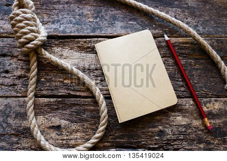 Running Knot And A Suicide Note On A Wooden Background