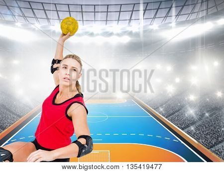 Female athlete throwing handball against handball field indoor