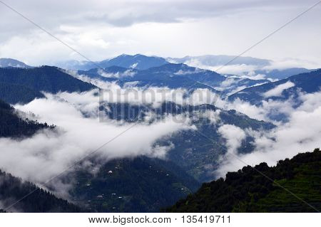 A peaceful picturesque misty morning over Himalayan mountain range in Shimla, Himachal Pradesh, India, Asia. Layers of hills are visible emerging from the mist shrouded valley. The mist here rolls in and out constantly.