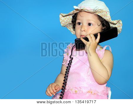 Two year old girl talking on the telephone isolated on blue.