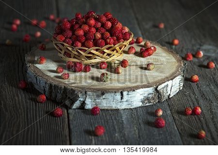 Fresh wild strawberry in a basket on an old wooden table