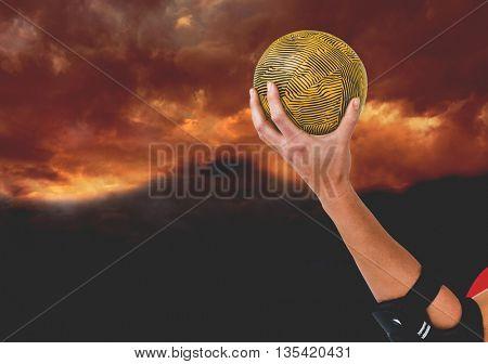 Female athlete with elbow pad holding handball against gloomy sky