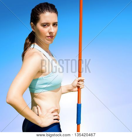 Portrait of serious sportswoman holding a javelin against blue sky