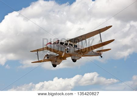 NORTHILL, UK - JULY 5: A vintage DeHavilland Rapide biplane gives short trips for paying customers during one of the air displays hosted at the Old Warden aerodrome on July 5, 2015 in Northill