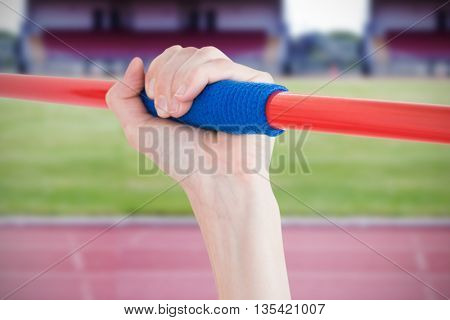 Female athlete throwing a javelin against race track