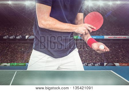 Mid section of athlete man playing table tennis against view of a stadium