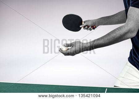 Male athlete playing table tennis against grey background