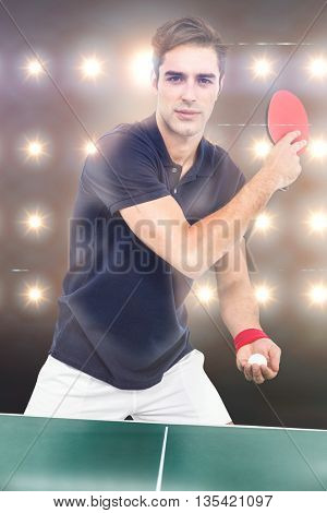 Confident male athlete playing table tennism against composite image of orange spotlight