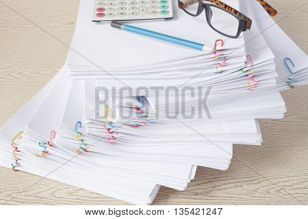 Pencil With Spectacles And Calculator On Stack Of Overload Paper