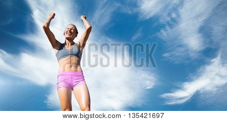 Low angle view of sportswoman celebrating her victory against blue sky with clouds