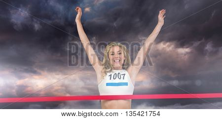 Portrait of cheerful winner athlete crossing finish line against gloomy sky