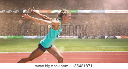 Sportswoman finishing her run against view of a stadium