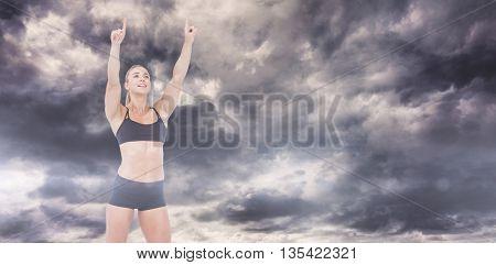 Female athlete raising fingers against gloomy sky