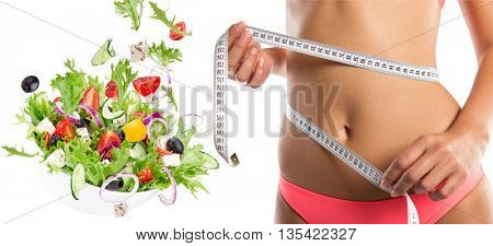 Slim girl measuring her waist with salad in motion.
