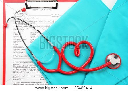 Red stethoscope and medical uniform with prescription, close up