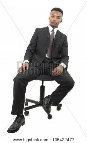 young man seated on computer chair wearing suit and tie