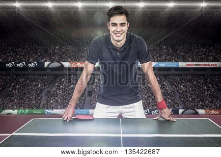 Confident male athlete leaning on hard table against view of a stadium