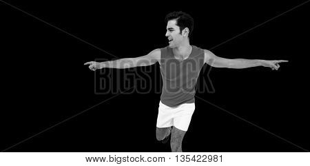 Excited male athlete with arms outstretched after victory on black background