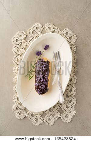 Eclair with chocolate ganache with candied lavender topping