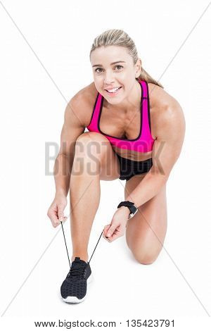 Female athlete tying her shoelace on white background