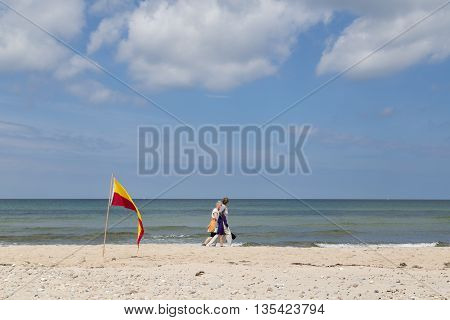 Tisvilde, Denmark - June 20, 2016: People walking behind red and yellow swimming area flag at Tisvilde beach.