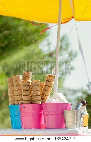 Cornets of ice cream under a yellow umbrella.
