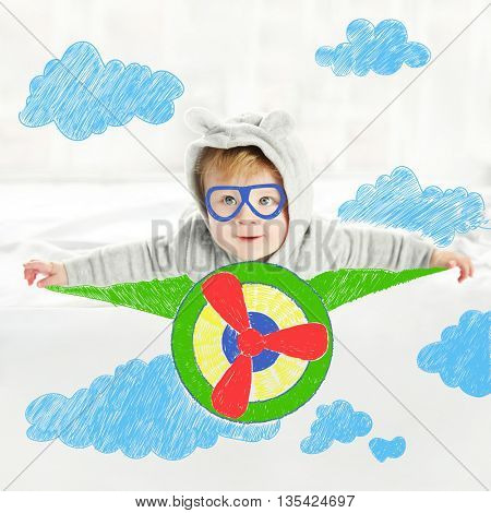 Little baby boy in grey pajamas flying on painted plane