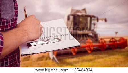 Cropped image of man with smartphone writing on book against view of a harvester