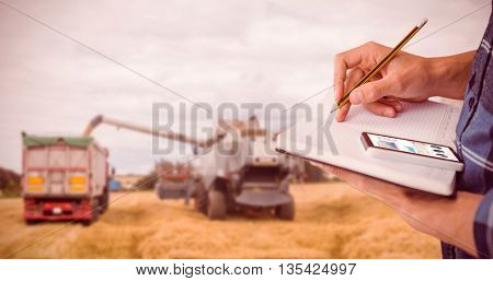Cropped image of man writing on diary with pencil against use of big harvester