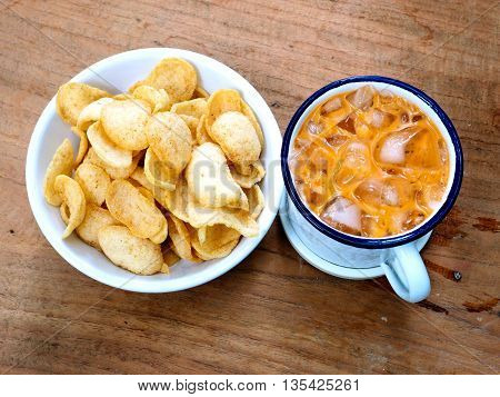 Thai tea in zinc cup white color line is blue and Prawn cracker snack on wood.