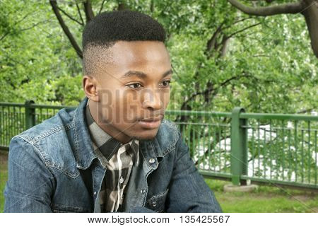 young black man in blue jeans outside in a park thinking and looking away