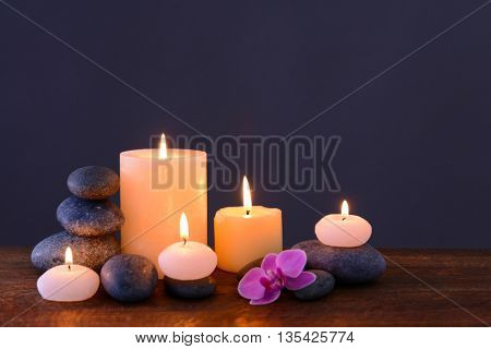 Spa stones with burning candles and flower on grey background